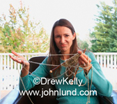 Picture of a woman holding some tangled up knitting, a real mess of yarn. She has long brown hair and a blue sweater on.